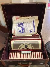 CELLINI ACCORDIAN IN HARD CASE WITH SHEET MUSIC