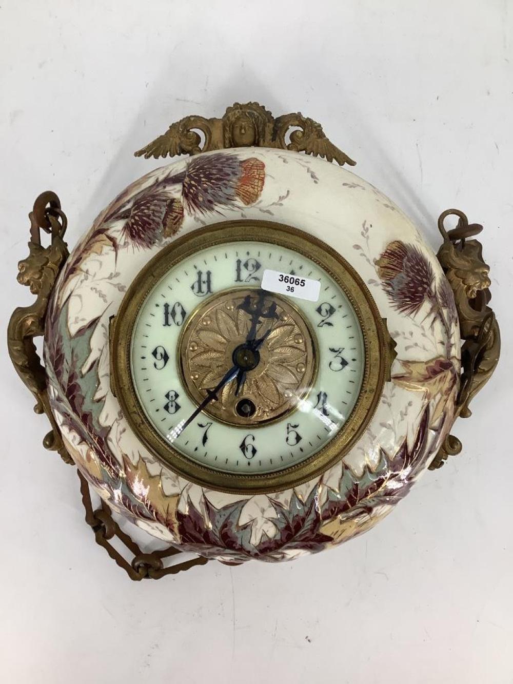 "Hanging China clock with porcelain dial and ormolu trim. 9 1/2""D"