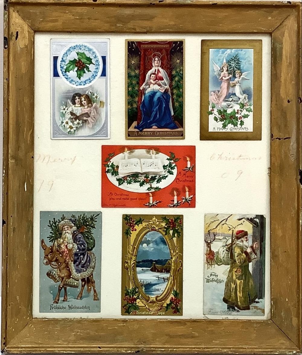 """Antique Christmas postcards in frame. Some in German. Some in English. Hand written script on cloth mat says """"merry Christmas 1909"""" 17"""" x 19"""" overall"""