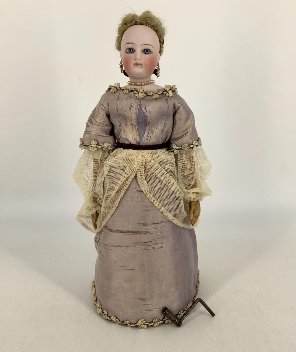 """Francois Gaultier French Fashion type Mechanical Lady. 12 1/2"""" bisque socket head doll on shoulderplate, mohair wig over cork pate, stationary glass eyes, pierced ears, closed mouth, on cloth covered cardboard body wi..."""