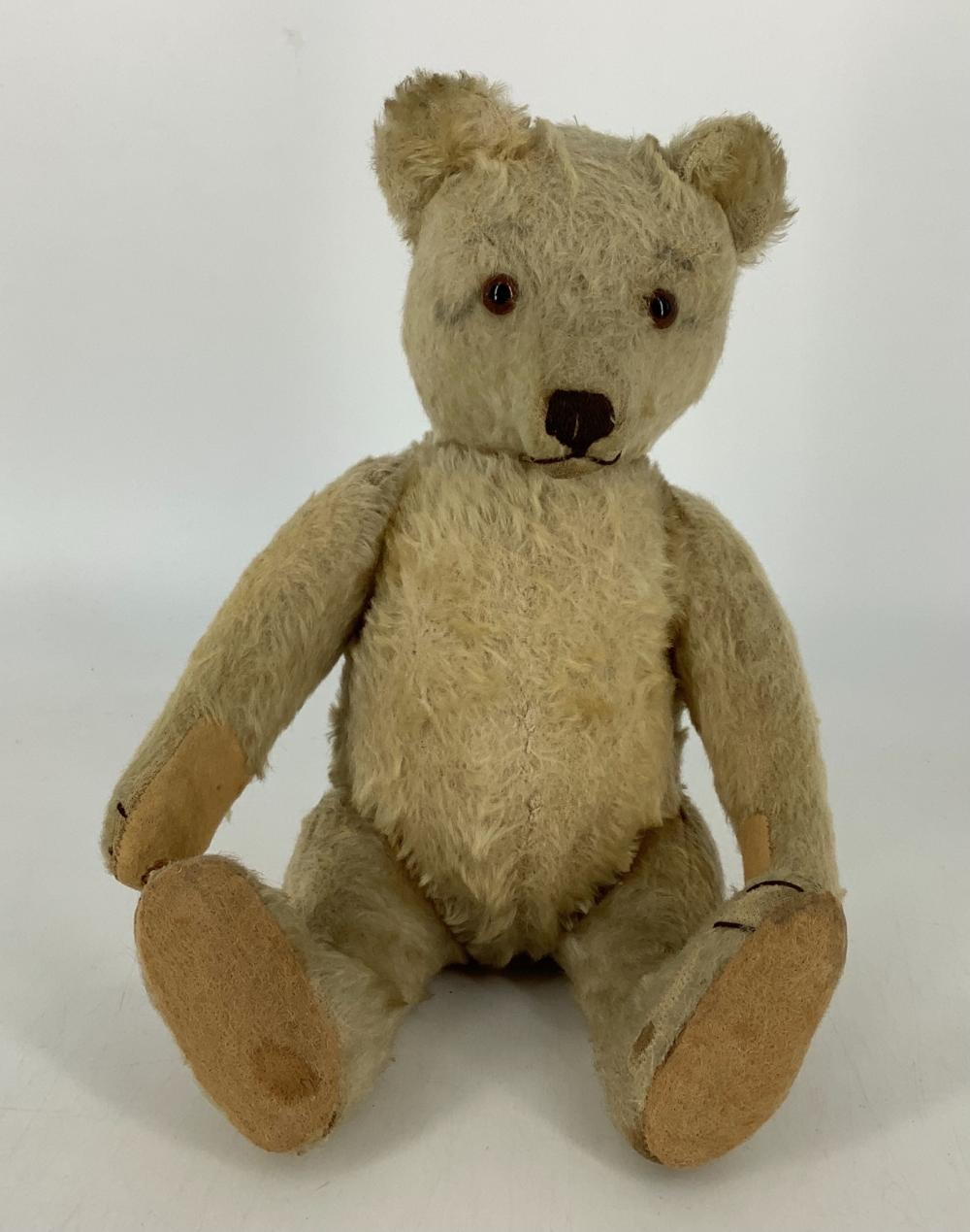 """Vintage Teddy Bear. Unmarked circa 1930's, 13"""" beige mohair bear with glass eyes, stitched nose, felt paw pads, disk jointed at neck, shoulders and hips. In overall good condition, retains most of his mohair, paw pads..."""