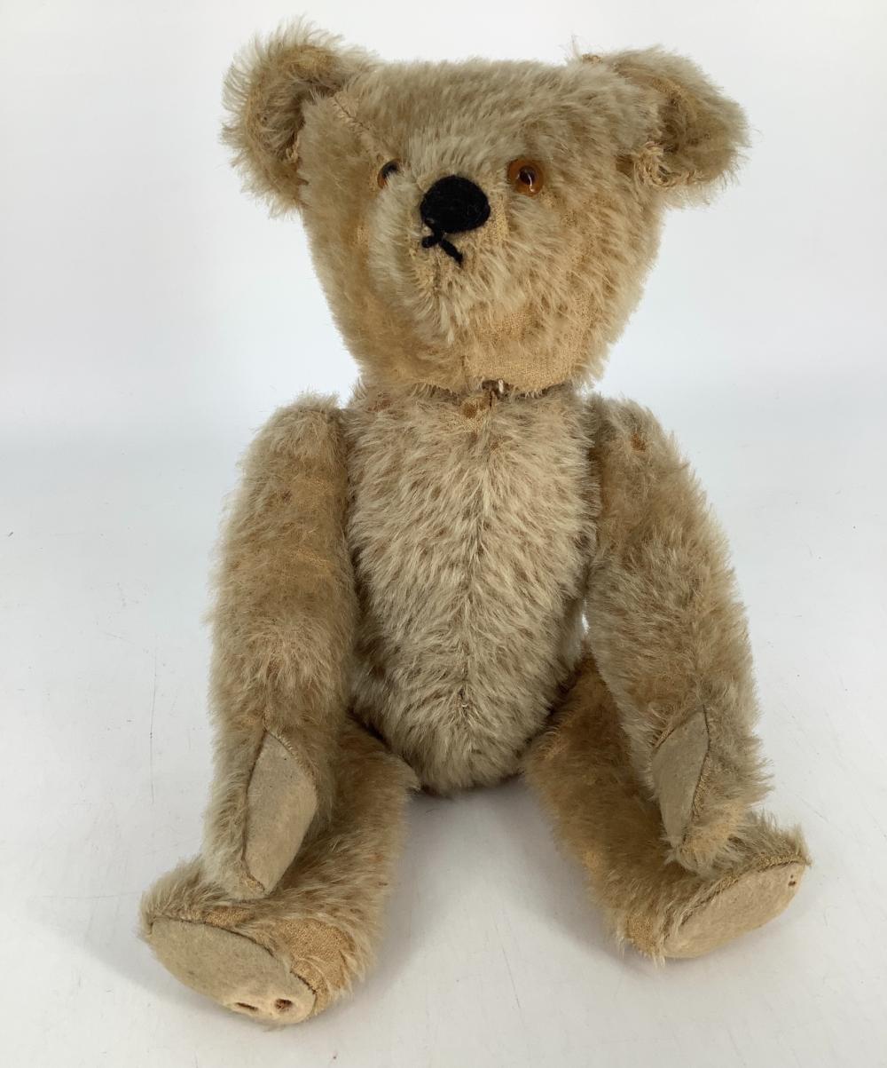 """Vintage unmarked Teddy Bear. 14 1/2"""" mohair bear with applied ears, glass eyes, short snout with stitched nose, disk jointed neck, shoulders and hips, felt paw pads. Mohair is sparse back of torso and arms, ears are p..."""