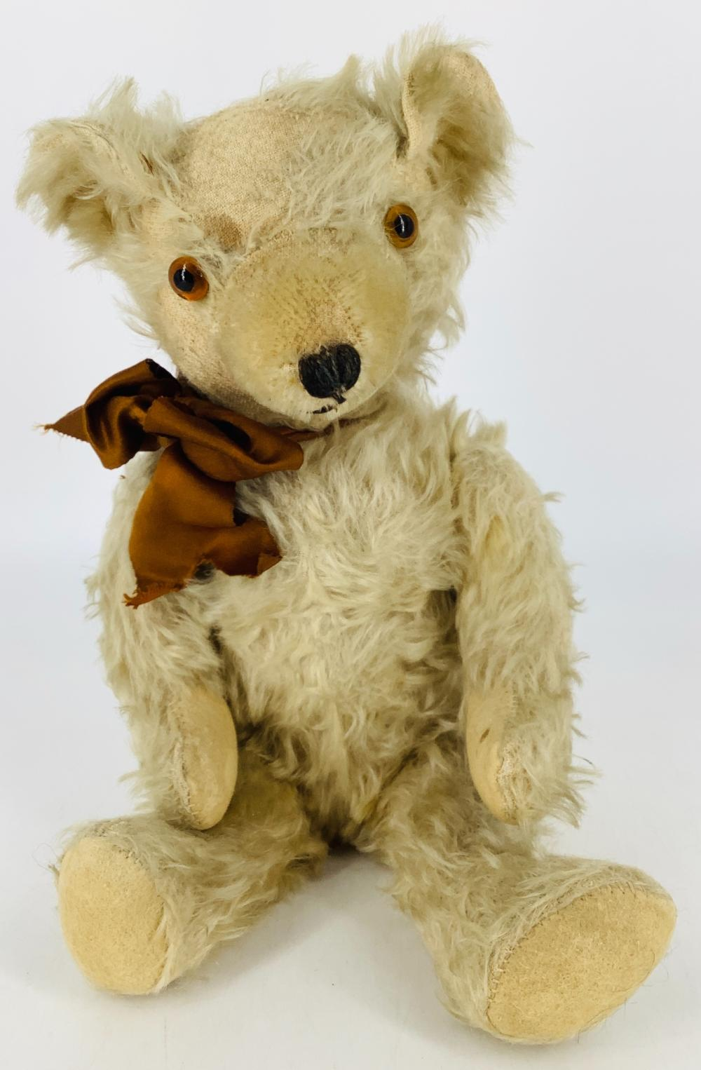 """Vintage blonde mohair teddy bear. 15 1/2"""" bear with applied ears, glass eyes, shaved snout with stitched nose, disk jointed at neck, shoulders and hips, felt paw pads. Mohair is worn and thin particularly on head and ..."""