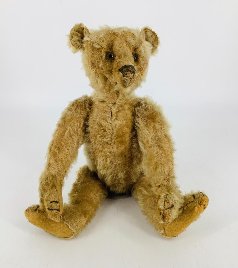 """Wonderful early Teddy Bear likely Steiff. 13"""" mohair bear, disk jointed at neck, shoulders and hips, glass eyes, long snout with stitched nose, applied ears, long arms and legs with felt paw pads, hump back torso. No ..."""