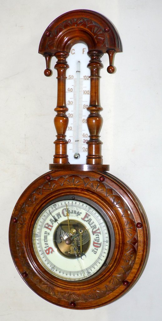 Victorian Carved Walnut Aneroid Barometer and Thermometer Circa1890s. Working order. Glass cracked. Length 17 inches.