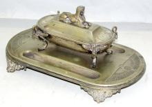 Antique Silver Plate EPNS Engraved Egyptian  Revival Ink Stand. 19thc. Having sphynx  handle to  the ink resevoir cover supported by Ibis topped  cabriolet legs on a double pen holder base with  decorative bracket feet. 11 3/4 x 6 3/4 inches.