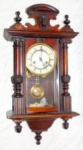 A Victorian Vienna Wall Clock with a 13cm white  dial by the Hamburg American Clock Company with a  two train gong striking movement the case with a  shaped mask pediment and undercut base. Working  Order. Height 26in.