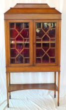 A Choice Edwardian Inlaid Mahogany and Satinwood  Display Cabinet. Early 1900's. Having a raised  tapering back above two astral glazed doors, red  velvet lined interior supported on tapering legs  and spade feet linked by a concave under shelf. Height 70in. Width 35.5in. Depth 14in.