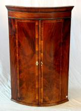 A Victorian Mahogany and Rosewood Crossbanded  Bowfront Hanging Corner Wall Cupboard. 19th  Century. Having a pair of well figured and band  inlaid doors with bone escutcheon enclosing three  shelves. Height 41in. Width 26.5in. Depth 19in.