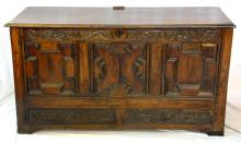 A 17th Century Carved Oak Coffer of geometric  panelled construction. Having a leaf and rose  carved top rail, triple panelled front leaf and  carved blind frieze drawer all supported on  bracket feet. Height 30in. Width 55in. Depth 20.5in.