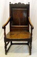 A 17th Century Oak Wainscoat Armchair. Having  rectangular panelled back with arched shaped  cresting,downswept open arms on baluster turned  supports embracing a 2 plank solid seat raised on  baluster turned legs joined by rectangular stretchers, Height 45 inches.