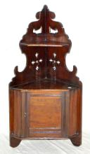A Victorian Simulated Mahogany Hanging Corner Wall  Cupboard. 19th Century. Having a pierced leaf  back above a panelled cupboard door. Height 30in.  Width 15.5in.