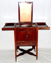 A George lV Mahogany Toilet Cabinet. Early 19thc.  The double hinged tray top enclosing five circular  apertures a rising mirror frame (lacking mirror)  over  2 cupboard doors and a drawer all supported  on tapering legs and original brass casters. Height 33 1/2 in.  Width 19 3/4in.Depth 18 in.