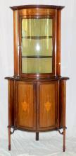 Edwardian Inlaid Mahogany Bow Fronted Corner  Display Cabinet. Early 1900s. The cavetto cornice  and deep inlaid freeze over the 2 bow fronted  glazed doors concealing 2 shelves. Below the 2 bow  fronted doors inlaid with urns all supported on tapered legs with spade feet.  Height 79 in.   Width 35 in. Depth 27 in.