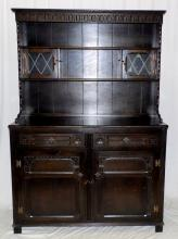 Vintage Old Charm Style High Back Dresser. 20th  Century. The top with a carved frieze over 2  leaded glass cupboard doors and three shelves  supported on a two drawer and two cupboard base on  style feet. Height 72in. Width 49in. Depth 19in.