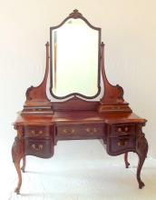 An Outstanding Victorian Queen Ann Style Carved Mahogany Dressing Table. 19thc.  The adjustable and removable beveled mirror above 2 jewel drawers on the intricately moulded top. The frieze with one long drawer flanked by two short drawers to either side with decorative gilded brass handles raised up on carved  cabriole supports. Height 76 in. Width 54.5 in.. Depth 25 in.
