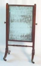 Antique Victorian Mahogany Cheval Mirror. Early 19thc. Having reeded supports linked with a turned cross stretcher on down swept legs on brass casters. Height 43.5 in Width 26 in.