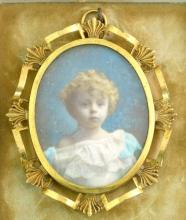 Portrait Miniature of a young child 3/4  length,over painted within an ornate leafy  gily frame. 5 1/2 cm in an outer easel hinged  frame.