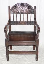 A 17th Century oak open arm chair with 6  turned spindels headed by an arch carved with  a leafy tree and flower heads.The downswept  arms on baluster and reel supports embracing  a 3 plank board seat on ring turned legs joined by rectangular section stretchers.  Some later additions. Height 39 inches.