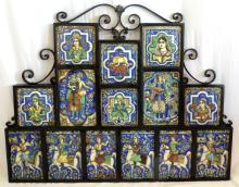 A Wrought-Iron Frame Containing Fourteen  Antique Islamic Tiles. Early 1900s. Six of  falconers on horseback, two of couples  playing musical instruments, four with female  portrait panels, another of a young man seated in a turban, another of a lion  attacking an animal. Each panel 9 x 6 inches  and smaller. 38 x 31 inches.