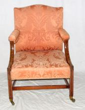A Good George III Library Mahogany Arm Chair.  Having stuffed arched back ,arms and  seat,the downswept arm supports carved with  beads and flutes,the square chamfered legs  joined by H stretcher terminating on brass casters. Height 39 inches.