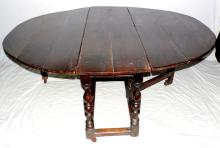 17thc Oak Double Gateleg Table. The oval  plank top above tulip and bobbin turned  uprights joined by stretchers and tie rails.  Supported on later brown pottery casters.  Length 60 in.  Width 69 to  20 in.  Height 27  in.