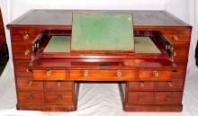 A Fine George IV Mahogany Double-sided  Secretaire Pedestal Desk.  The moulded top  with inset tooled black leather writing  surface. Below to one side is a secretaire  drawer enclosing a sliding baize lined adjustable writing slope and 8 pigeon  holes,lidded compartments above an  arrangement of 13 drawers.The reverse with 6  false drawers 4 short drawers and a pair of  cupboards one fitted for folios the other with 3 drawers all raised upon a plinth base.   Height 36 in. Width 68 in. Depth 37 in.