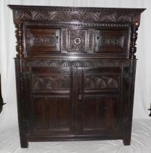 A Fine English Carved Oak Court Cupboard. Mid  17thc.. The lunette carved cornice/ freeze  above two tudor rose carved doors and central  panel flanked by turned supports and shelf.  The lower section with two doors all standing  on stile supports. Height 66 in.  Width 56.5  in.  Depth 22.25 in.