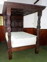 A Period Carved Oak and Chequer-Lined Tester  Bed. Having pannelled headboard with Male and  Female Caryatids centred by chequer-Inlaid  panels within net borders centred by further  inlaid panels of birds within scrolling foliage, The moulded foot/side rails and  pannelled canopy with moulded overhanging  cornice carved with lunettes and foliage  supported by turned fluted and foliate-carved  coloumns on moulded square supports. Incorporating some 17th Century elements,  restorations, with base and mattress. Height  80 in, Width 62in. Length 81 in