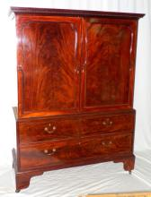 A George III Mahogany Wardrobe with a dentil  cornice above a pair of well figured panelled  doors,moulded apron above 2 short and 1 long  false drawer,raised on bracket feet. 178 x  133 x 52 cm.