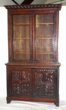 A Good 19th Century Carved Oak Bookcase.  Having leaf and berry pediment,above glazed  cabinet doors embraced with a celtic knot  decoration to the frames. Below  the two  cabinet doors finely carved with 8 panels depicting oak & acorn leaves,flowers and  foliage all supported on carved leafy bracket  feet.  Height 85 in. Width 36 in. Depth 18  in.