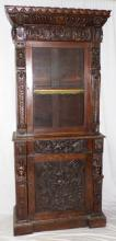 A Rare Oak Bookcase 19thc with 17thc  Additional Carvings. The substantional  cornice with pyramid moulding over lobed  /leaf designs above a deep freize with lions  masks and foliate. The glazed cabinet doorflanked by 17thc oak caryatids supported on  scaly columns.Below a single drawer and  panelled cupboard door both profusely carved  with a central knights armet and leafy  backdrop again flanked by 17thc oak caryatids. All raised on an inverted plinth  base. Height 85 in. Width 36 in. Depth 18 in.