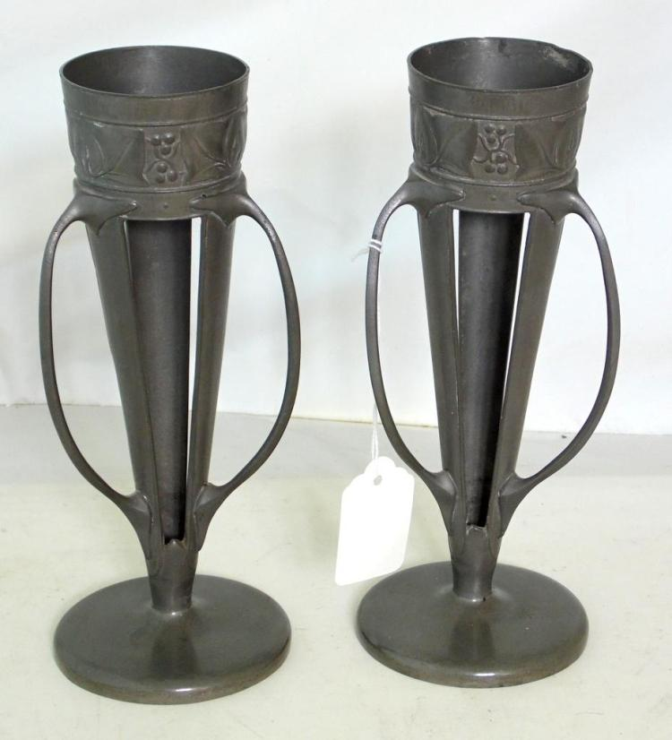 A PAIR OF LIBERTY & CO TUDRIC PEWTER VASES DESIGNED BY ARCHIBALD KNOX. Having an embossed band of ivy leaves above stylised handles on a circular base, impressed marks and 0957 to base. Height 22 cm. (2 Items) Liners missing.