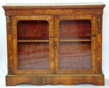 Early Victorian 2 Door Marquetry Inlaid Walnut Display Cabinet. 19thc. The book matched veneered top over 2 glazed doors enclosing the original red velvetine interior flanked by gilt bronze figural and leaf decoration. Supported on a shaped plinth base.  Height 43 in. Width 52 in.  Depth 14 in.