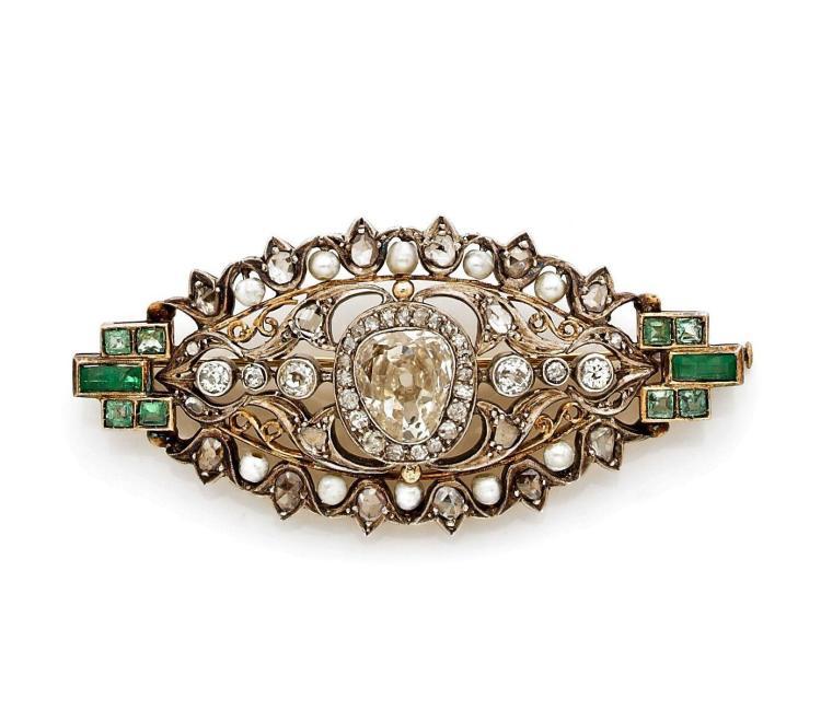 BROCHE LOSANGE en alliage d'or jaune ajouré de culots et de rinceaux sertis de diamants taillés en rose, de perles fines et d'émer...