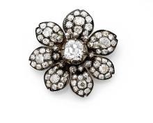 BROCHE FLEUR En argent et or jaune 18k (750), ornée au centre d'une fleur à sept pétales, au centre, orné d'un diamant taillé en c...