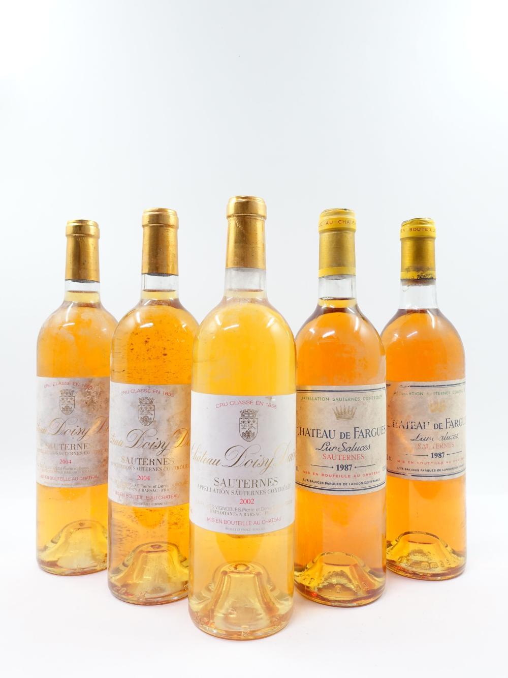 5 bouteilles 2 bts : CHÂTEAU DE FARGUES 1987 Sauternes (1 base goulot, 1 légèrement bas. Étiquettes tachées, léger déchirées) 1 b...
