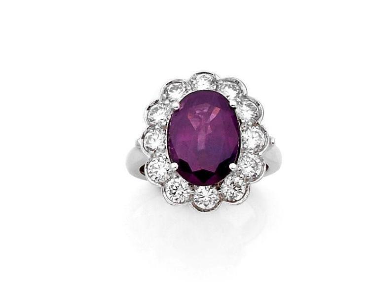 BAGUE en or gris ornée d'un saphir bleu-pourpre ovale entouré de diamants taillés en brillant. Poids de la pierre : 5,44ct. Accomp....