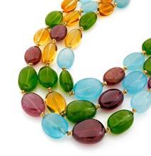 COLLIER Formé de trois rangs de perles d'améthystes, de tourmalines vertes, d'aigues marines et de citrines, les intercalaires et...