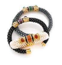 MARINA B TROIS BRACELETS SEMI-RIGIDES En or jaune 18k (750) et acier, formés chacun d'un jonc tissé de perles de culture, boules...