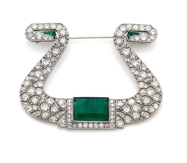 A DIAMOND, EMERALD, PLATINUM AND WHITE GOLD LYRE BROOCH, CIRCA 1930