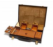 HERMES Paris Une mallette de voyage en box marron, garniture en métal plaqué or, intérieur comprenant deux brosses à habits, deux...