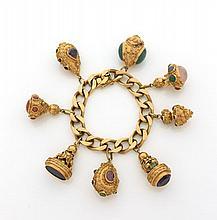 BRACELET A MAILLE GOURMETTE en or jaune retenant huit breloques cachets ou lanternes ornés de pierres fines (accidents). Long. :...