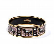 HERMES Paris made in austria Bracelet large en métal plaqué or et émail, à décor de chevaux sur fond noir. Diam.: 6,5 cm.  A...