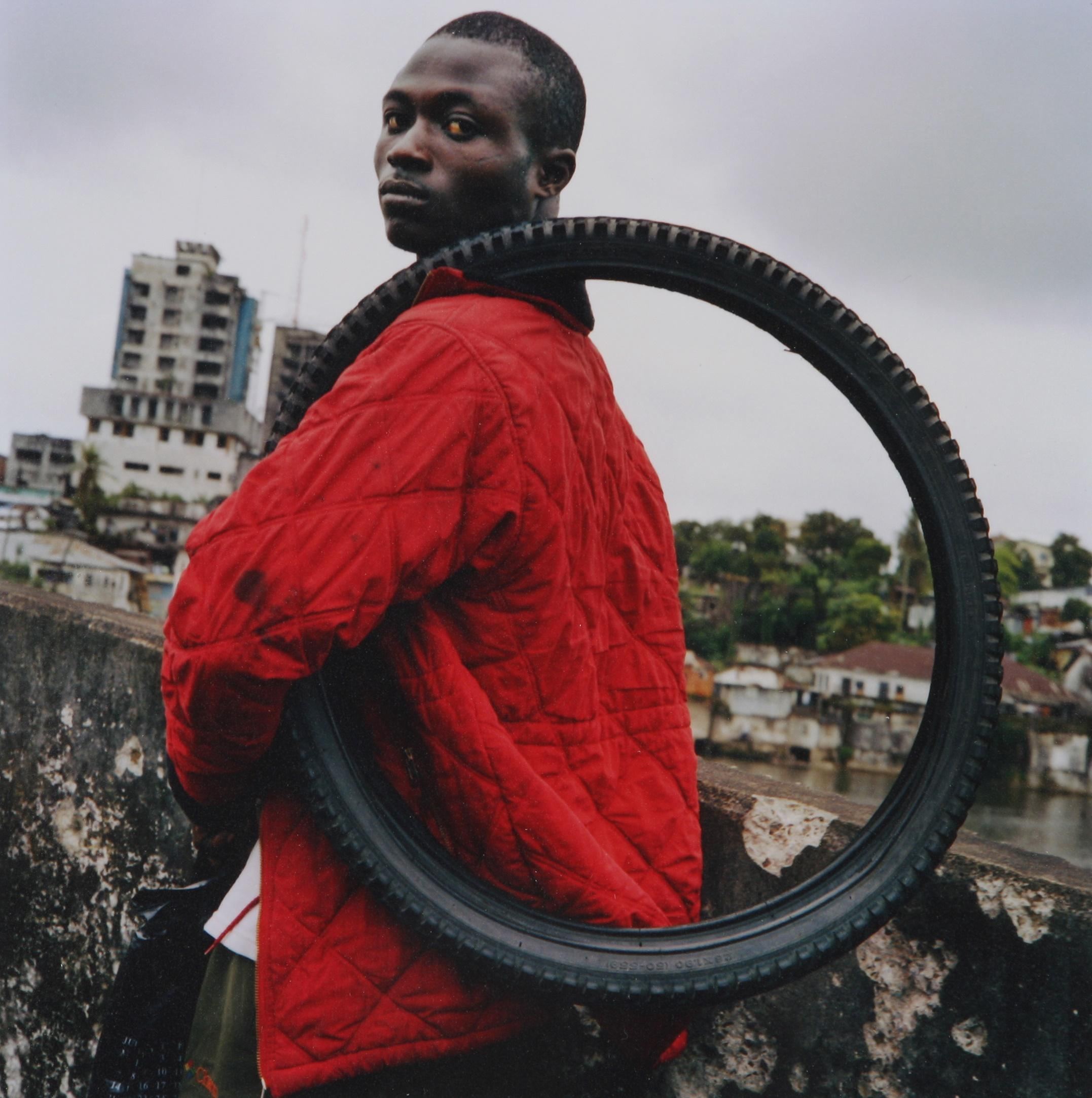 Tim Hetherington (Britain 1970-2011) Liberia 2003. A young man on the Gabriel Tucker bridge in central Monrovia carries a tyre which he is trying to sell.