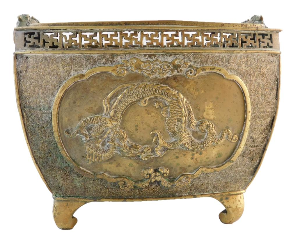 ASIAN: Bronze jardinere, square vessel raised on four feet with serpent handles, punched angular rim, non-handle sides depict dragon...