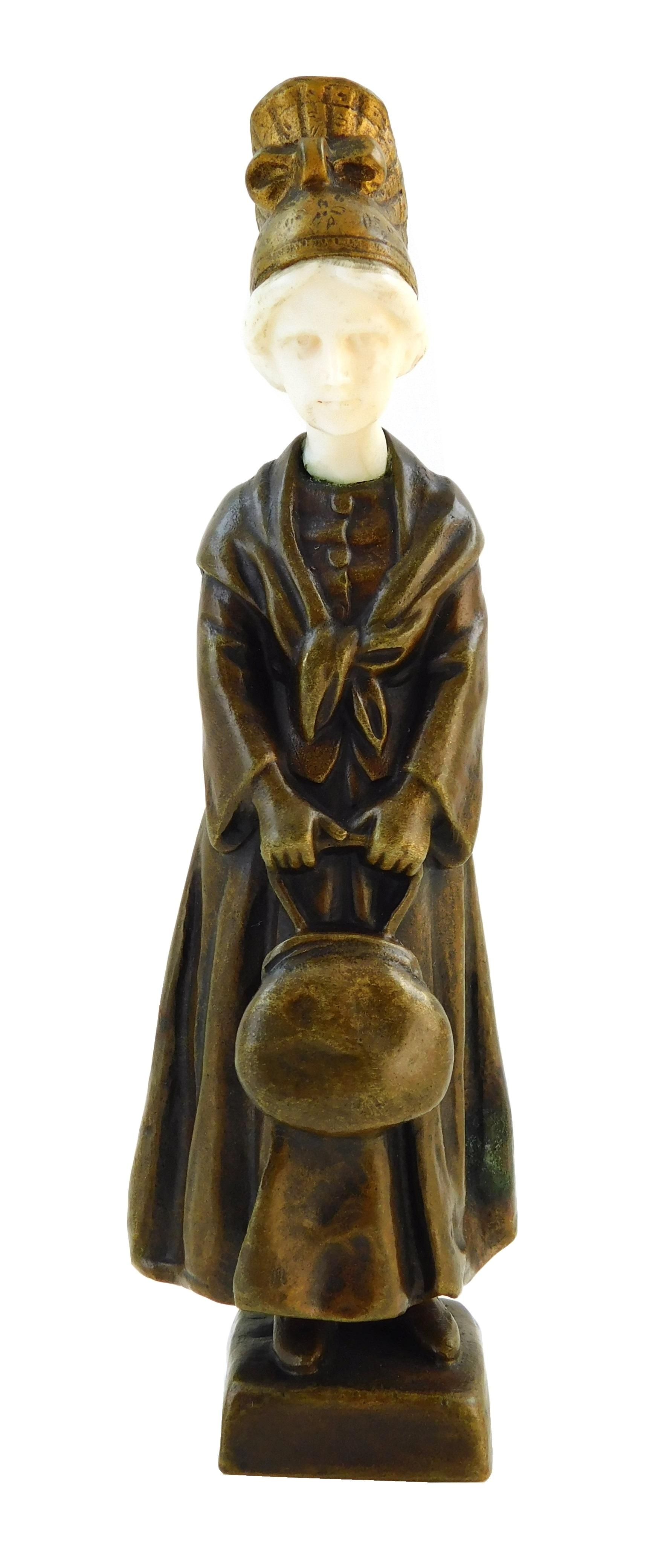 Peter Tereszczuk (Austrian, 1874-1963), figural bronze with carved head, depicting standing young female in coat and hat holding han...