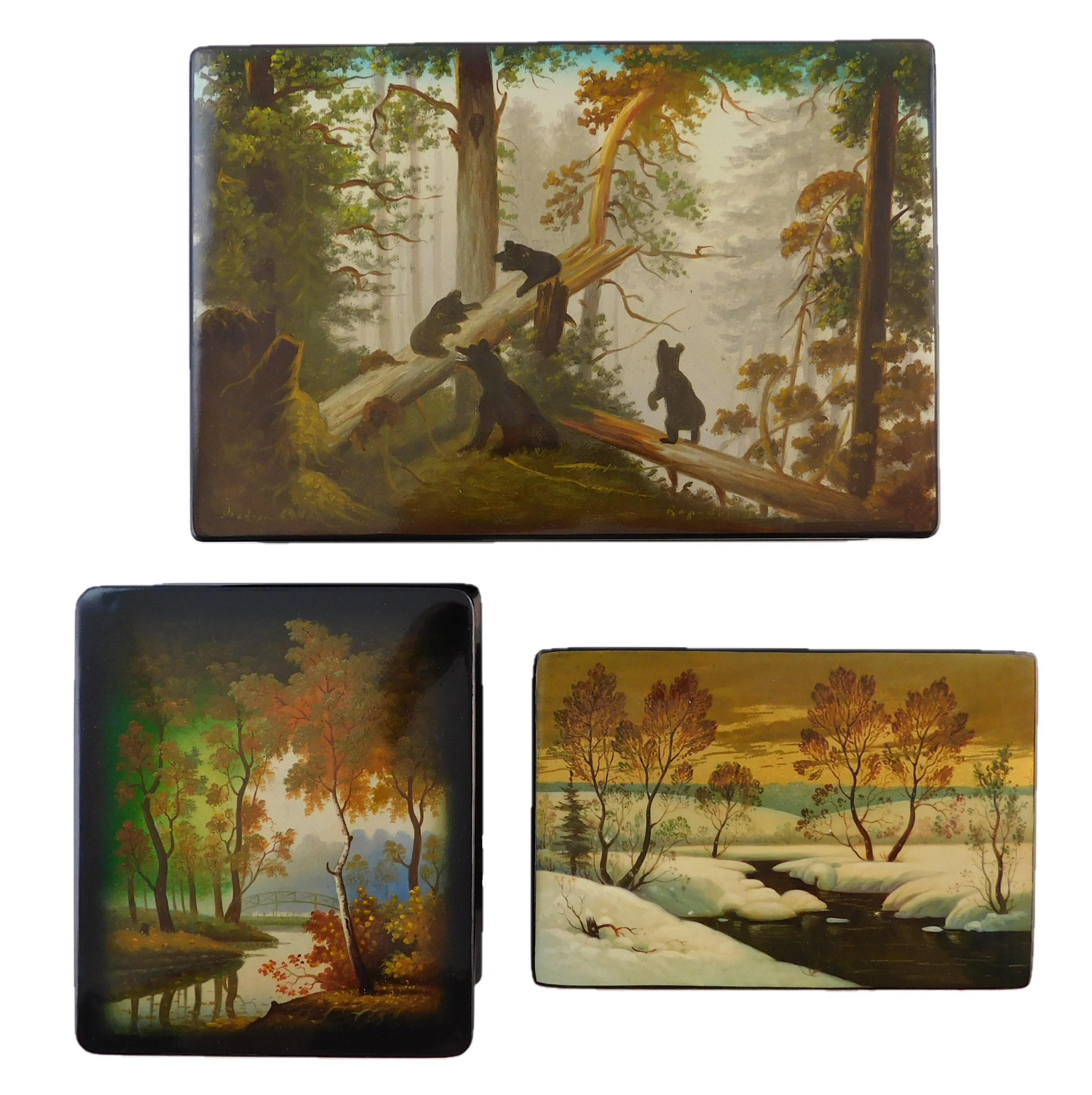 """Russian hand-painted lacquer boxes, three pieces, nature/ landscape themed, 20th C., details include: """"Morning in the Woods"""" after o..."""