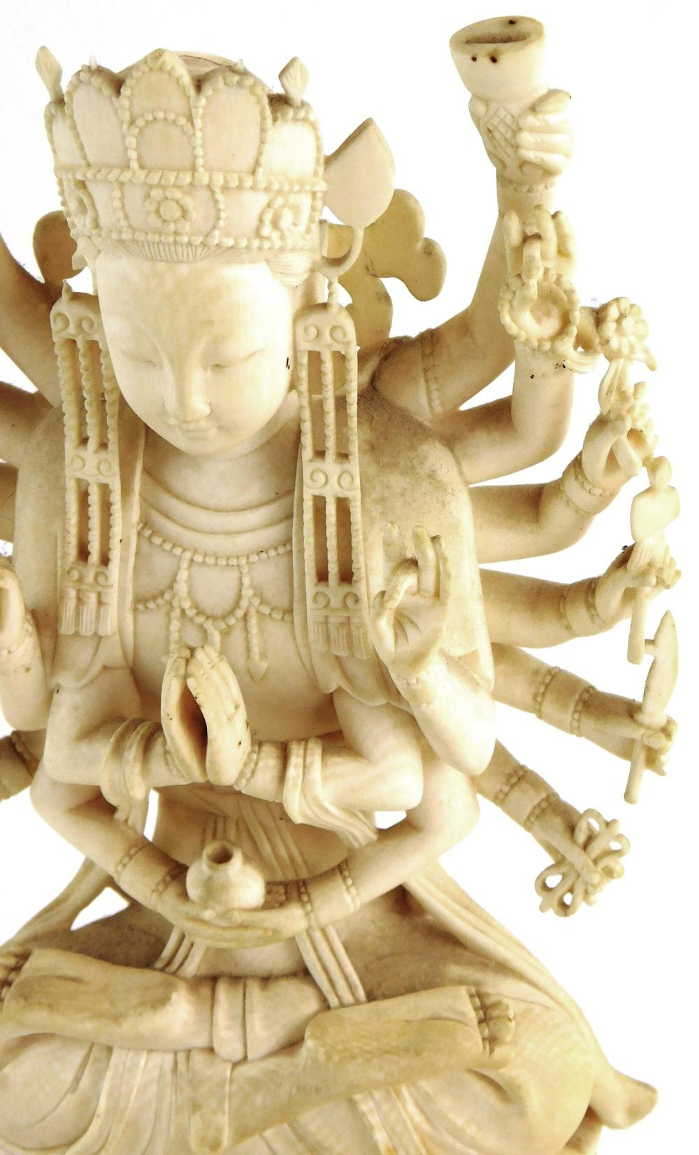 ASIAN: Carved ivory Hindu or Buddhist deity, early to mid-20th C., depicted with eighteen arms and seated on lotus flower, ornately...