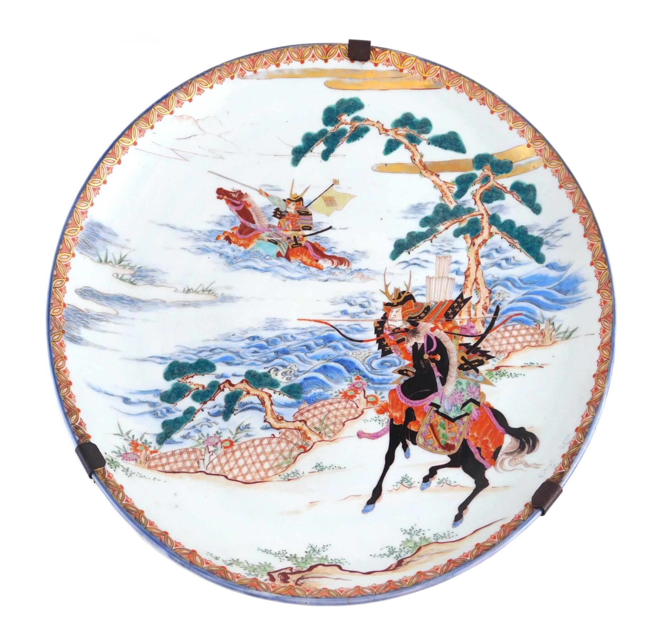ASIAN: Japanese porcelain charger, 19th C. - 20th C., polychrome decorated with samurai on horseback, wear consistent with age and u...